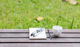 Monokel, anteckningsbok med blyertspennan och kaffe på trätabellen i arkivfoton