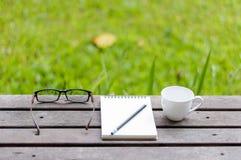 Monokel, anteckningsbok med blyertspennan och kaffe på trätabellen i royaltyfri foto