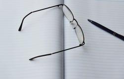 Monokel och penna på boken arkivbilder