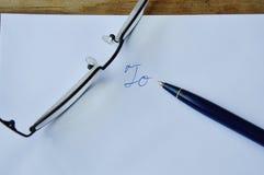 Monokel och penna på det vita kuvertet fotografering för bildbyråer