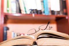 Monokel på öppnade boksidor, bokhylla på den blurried bakgrunden, utrymme för text royaltyfri fotografi