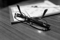 Monokel på fokus, korsord och en penna på den suddiga bakgrunden, på trätabellen arkivbild