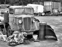 Monokrom bild av en gammal rosta lastbil med restträ och metall i en lantlig skrot royaltyfria foton