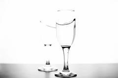 Monokromt foto av champagne på den vita tabellen på vit bakgrund Arkivbilder