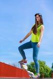 Monopatín adolescente del montar a caballo del patinador de la muchacha en la calle Foto de archivo