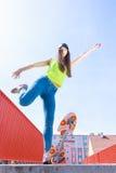 Monopatín adolescente del montar a caballo del patinador de la muchacha en la calle Imagenes de archivo
