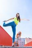 Monopatín adolescente del montar a caballo del patinador de la muchacha en la calle Fotografía de archivo libre de regalías