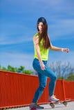 Monopatín adolescente del montar a caballo del patinador de la muchacha en la calle Foto de archivo libre de regalías