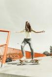Monopatín adolescente del montar a caballo del patinador de la muchacha en la calle Imagen de archivo