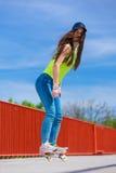 Monopatín adolescente del montar a caballo del patinador de la muchacha en la calle Fotografía de archivo