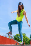 Monopatín adolescente del montar a caballo del patinador de la muchacha en la calle Imágenes de archivo libres de regalías