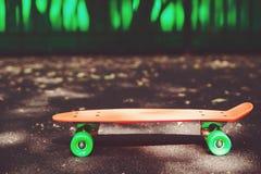 Monopatín anaranjado del penique en el asfalto detrás de la pared verde Fotos de archivo