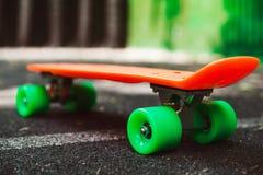 Monopatín anaranjado del penique en el asfalto detrás de la pared verde Fotos de archivo libres de regalías