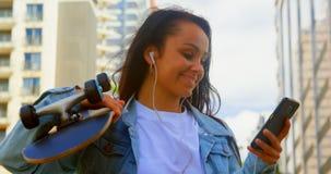 Monopatín de la tenencia de la mujer joven mientras que usa el teléfono móvil en la ciudad 4k metrajes