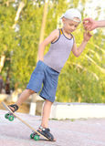 Monopatín del entrenamiento del niño del muchacho Foto de archivo