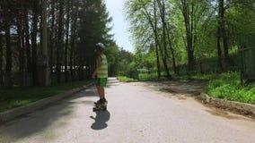 Monopatín del montar a caballo del niño en día de verano
