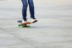 Monopatín del montar a caballo del skater de la mujer en ciudad Fotos de archivo