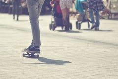 Monopatín del montar a caballo del skater en el pavimento de la calle de la ciudad Fotos de archivo libres de regalías