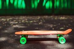 Monopatín del penique en el asfalto detrás de la pared verde Imagenes de archivo