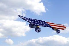 Monopatín del vuelo con la bandera de los E.E.U.U. en el cielo azul y las nubes Fotos de archivo libres de regalías