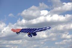 Monopatín del vuelo con la bandera de los E.E.U.U. en un cielo azul y las nubes Fotos de archivo