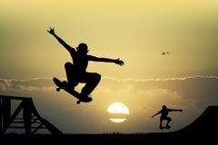 Monopatín en la puesta del sol Fotos de archivo