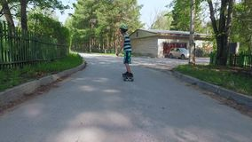 Monopatín joven del montar a caballo del muchacho en día de verano