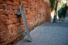 Monopatín que se inclina contra la pared hecha de ladrillos anaranjados Fotografía de archivo libre de regalías