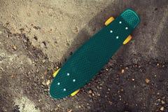 Monopatín verde en el fondo del asfalto texturizado Imagen de archivo libre de regalías