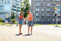 Monopatines adolescentes del montar a caballo de los pares en la calle de la ciudad Fotos de archivo libres de regalías