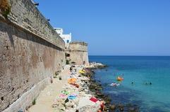 MONOPOLI,意大利- 2017年8月4日:海滩夏令时的人们在亚得里亚海, Monopoli,意大利 免版税库存图片