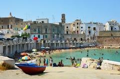MONOPOLI,意大利- 2017年8月4日:海滩夏令时的人们在亚得里亚海, Monopoli,意大利 免版税图库摄影