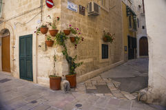 Monopoli, Puglia, Italy - beautiful alley. Monopoli, Puglia, Italy - beautiful street with flowers on the building`s corner Royalty Free Stock Image
