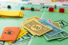 Monopoly board game in play. Monopoly board game cards and pieces Royalty Free Stock Photography