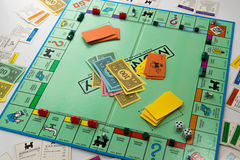 Monopoly board game in play. Monopoly board game cards and pieces Royalty Free Stock Photos