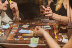 Monopoly. LUTSK, UKRAINE - 17 February 2017: Friends playing board game together in club stock images