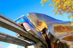 Monorail and EMP Museum. SEATTLE, WASHINGTON - October 25, 2016: The Monorail train passing through the ultra-modern EMP Museum on sunny fall morning Royalty Free Stock Image