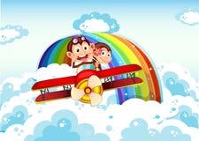 Monos juguetones que montan en un avión cerca del arco iris Imagenes de archivo