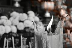 Monotone style background. Burning candles and flowers for worship. And empty left space for text royalty free stock image