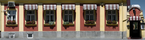 Monotonous windows. With striped awnings shadows as part of an old building Royalty Free Stock Images
