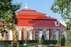 Monplaisir宫殿在Peterhof,包围由绿色树、灌木和花 免版税图库摄影