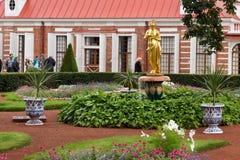 Monplezirsky arbeta i trädgården, en springbrunnklocka med en staty av Psiheya Arkivfoto
