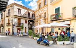 People enjoying a street bar in the historic center of Monreale, Sicily. Monreale, Palermo, Italy - October 8, 2017: People enjoying a street bar in the historic Royalty Free Stock Photo