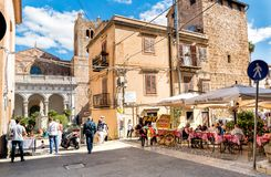 People enjoying a street bar in the historic center of Monreale, Sicily. Monreale, Palermo, Italy - October 8, 2017: People enjoying a street bar in the historic Stock Image