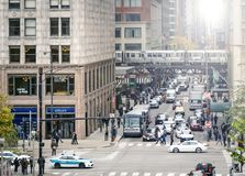 Monroe Street at the intersection with Michigan Avenue in rush hour in the financial district of Chicago