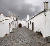Monsaraz street. Typical street of white houses of Monsaraz under an overcast sky. Alentejo, Portugal Royalty Free Stock Images