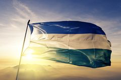 Monsenor Nouel Province of Dominican Republic flag textile cloth fabric waving on the top sunrise mist fog. Beautiful royalty free stock photography