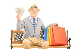 Monsieur de sourire s'asseyant sur un banc avec des sacs et tenir l'argent Photographie stock