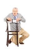 Monsieur effrayé se cachant derrière une chaise en bois Images stock
