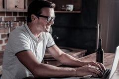 Monsieur instruit travaillant sur l'ordinateur portable à la maison photographie stock libre de droits